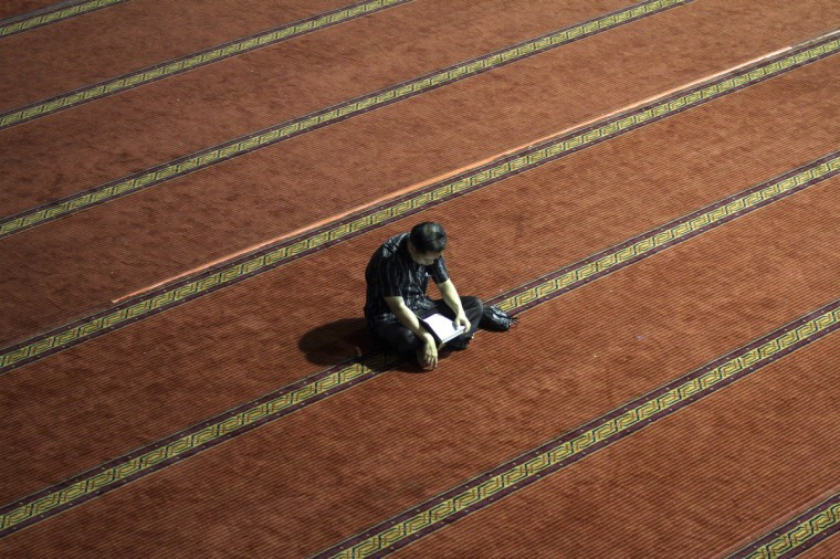 An Indonesian Muslim man reads the Quran at a mosque on July 9, 2013 in Jakarta, Indonesia. Muslims must fast in the month of Ramadan from dawn until sunset, when they break the fast with the meal known as Iftar. (Syamsul Bahri Muhammad/Getty Images)