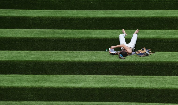 A man reads a book in the sunshine on steps covered in artificial grass in London, England. (Oli Scarff/Getty Images)