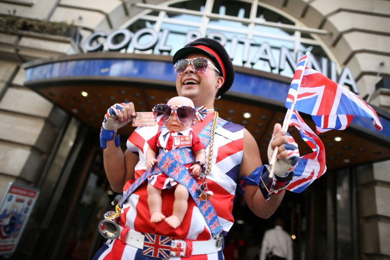 Promotions manager Daniel Obando wears a baby doll wrapped in union flag decorations as he stands in Piccadilly as the UK prepares for the birth of the first child of The Duke and Duchess of Cambridge in London, England. (Peter Macdiarmid/Getty Images)