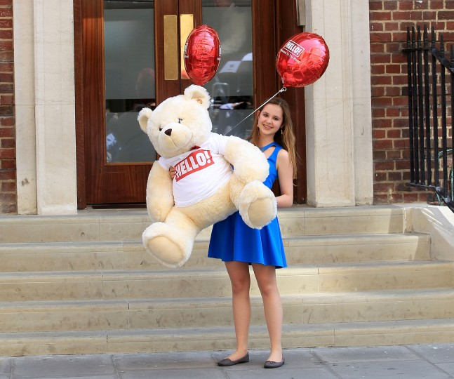 A Hello magazine promo girl brings a teddy to the hospital as the UK prepares for the birth of the first child of The Duke and Duchess of Cambridge in London, England. (Danny E. Martindale/Getty Images)