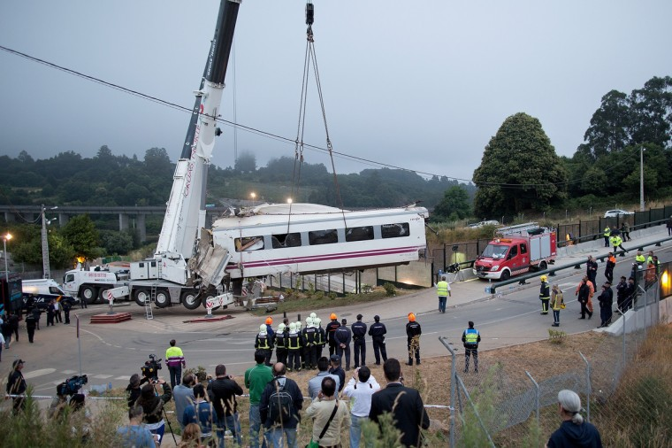A wagon of a crashed train that killed at least 77 people is lifted on July 25, 2013 at Angrois near Santiago de Compostela, Spain. The crash occurred on Wednesday at 8.40pm as the train approached the north-western Spanish city of Santiago de Compostela, with 247 passengers on board. At least 77 people have died and a further 131 have been reported injured. The crash occured on the eve of Santiago de Compostela's main religious festival. (Pablo Blazquez Dominguez/Getty Images)