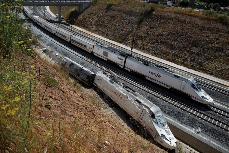 The first Madrid-Ferrol train service since the accident passes next to the wreckage of the previous one on July 26, 2013 in Santiago de Compostela, Spain. The high speed train crashed after it derailed on a bend as it approached the north-western Spanish city of Santiago de Compostela at 8.40pm on July 24th. At least 78 people have died and a further 131 are reported injured. The crash occured on the eve of the Santiago de Compostela Festivities. (Pablo Blazquez Dominguez/Getty Images)