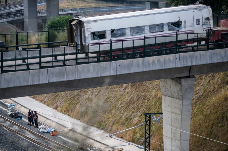 A truck carrying part of wreckage on a bridge over the track , on July 26, 2013 in Santiago de Compostela, Spain. The high speed train crashed after it derailed on a bend as it approached the north-western Spanish city of Santiago de Compostela at 8.40pm on July 24th. At least 78 people have died and a further 131 are reported injured. The crash occured on the eve of the Santiago de Compostela Festivities. (David Ramos/Getty Images)