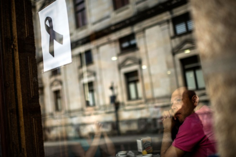 A man looks on from a cafe as a poster with a black ribbon on is displayed on the window in memory of the victims of the train crash , on July 26, 2013 in Santiago de Compostela, Spain. The high speed train crashed after it derailed on a bend as it approached the north-western Spanish city of Santiago de Compostela at 8.40pm on July 24th. At least 78 people have died and a further 131 are reported injured. The crash occured on the eve of the Santiago de Compostela Festivities. (David Ramos/Getty Images)