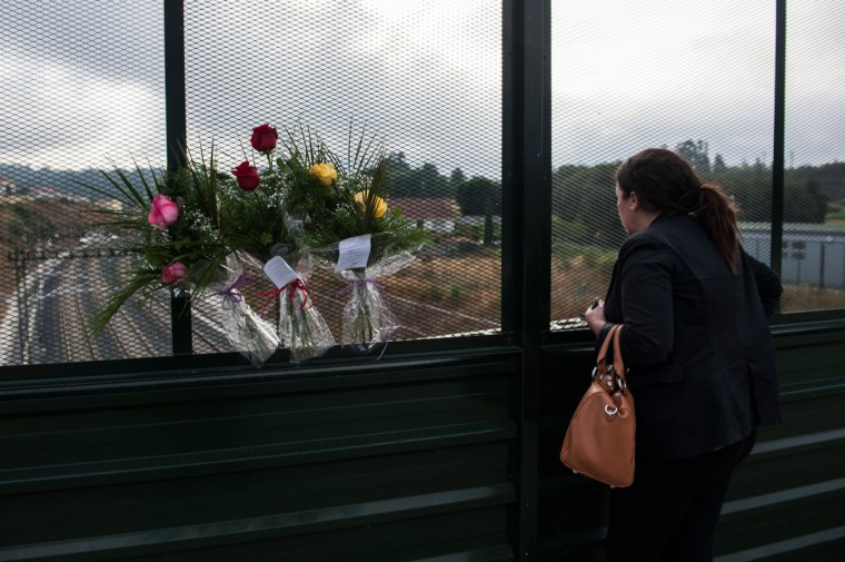 A woman looks on from a bridge over the rail next to flowers to remember the victims of a train crash that killed 78 people on July 26, 2013 in Santiago de Compostela, Spain. The crash occurred as the train approached the north-western Spanish city of Santiago de Compostela at 8.40pm on July 24th, at least 78 people have died and a further 131 reported injured. The crash occured on the eve of the Santiago de Compostela Festivities. (David Ramos/Getty Images)