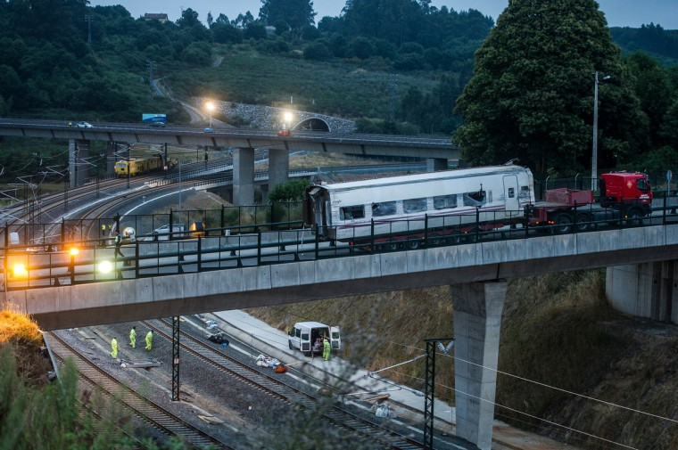 Workers at the train crash scene as a carriage is transported away on July 26, 2013 in Santiago de Compostela, Spain. The crash occurred as the train approached the north-western Spanish city of Santiago de Compostela at 8.40pm on July 24th, at least 78 people have died and a further 131 reported injured. The crash occured on the eve of the Santiago de Compostela Festivities. (David Ramos/Getty Images)