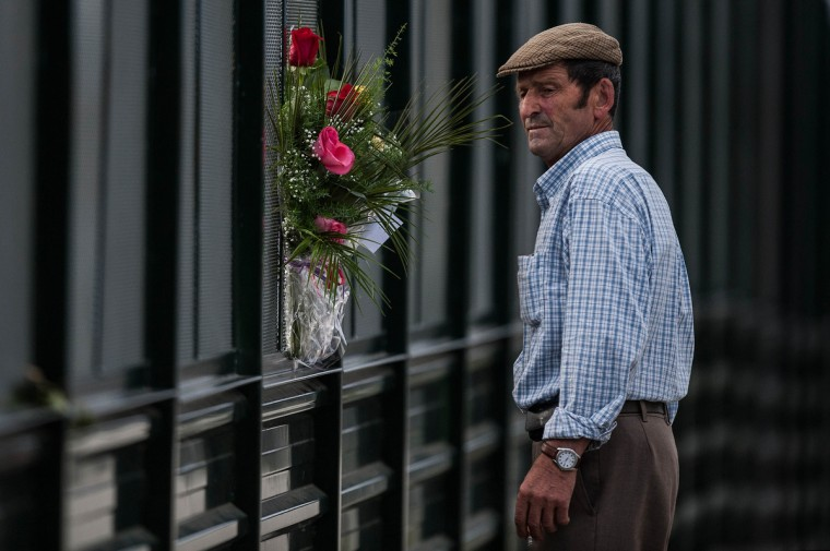 A man looks on from a bridge over the track next to flowers to remember the victims of a train crash that killed 78 people on July 26, 2013 in Santiago de Compostela, Spain. The crash occurred as the train approached the north-western Spanish city of Santiago de Compostela at 8.40pm on July 24th, at least 78 people have died and a further 131 reported injured. The crash occured on the eve of the Santiago de Compostela Festivities. (David Ramos/Getty Images)