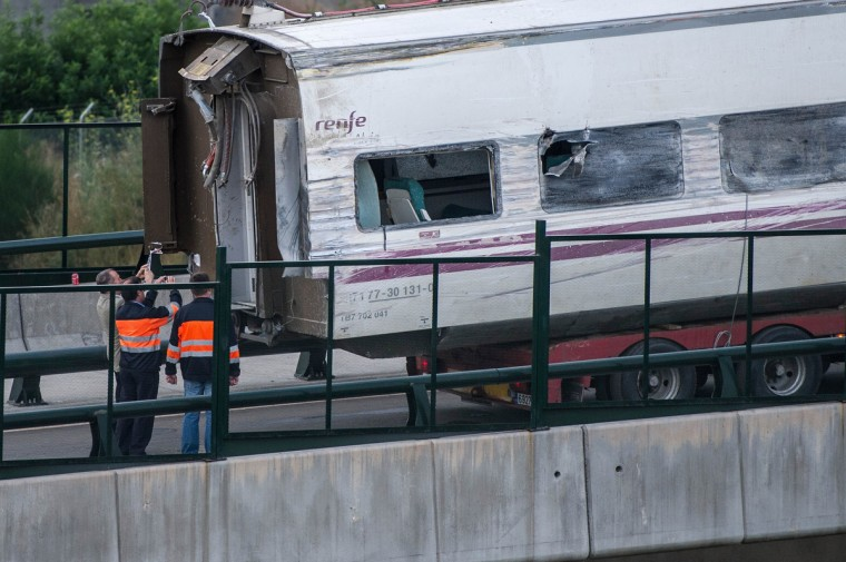 Technicians take pictures of a carriage from the crashed train on a bridge over the track on July 26, 2013 in Santiago de Compostela, Spain. The crash occurred as the train approached the north-western Spanish city of Santiago de Compostela at 8.40pm on July 24th, at least 78 people have died and a further 131 reported injured. The crash occured on the eve of the Santiago de Compostela Festivities. (David Ramos/Getty Images)