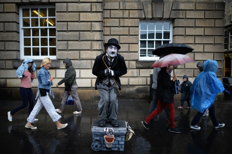 Members of the public, walk past a street entertainer on the Royal Mile in Edinburgh, Scotland. The city is preparing ahead of the Edinburgh Fringe Festival which runs from the 2 -26 August and is one of the largest arts festivals in the world, dating back to 1947. The festival attracts thousands of performers from across the world to showcase their acts in Scotland's capital. (Jeff J Mitchell/Getty Images)