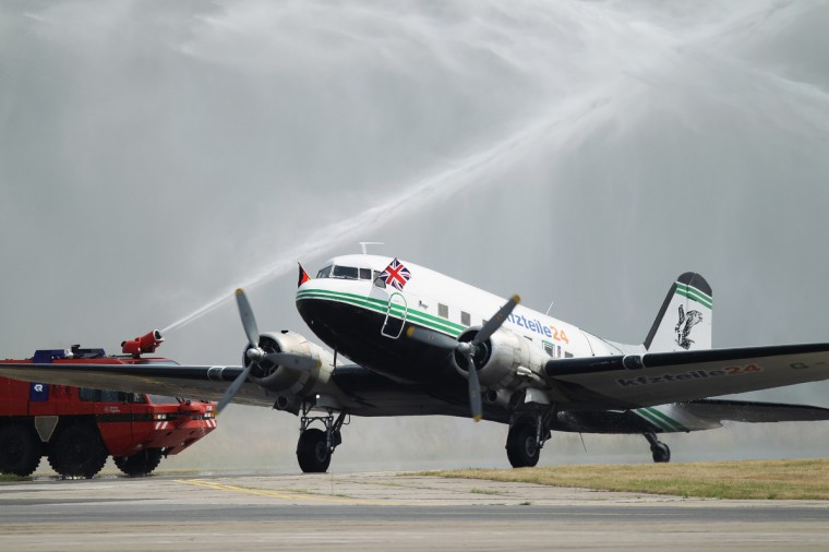 Fire trucks spray water in celebration over a vintage DC-3 plane that once participated n the Berlin Airlift and will be part of the Candy Bomber program upon its arrival at Schoenefeld Airport near Berlin in Schoenefeld, Germany. The original Candy Bomber, in German called the Rosinenbomber, also took part in the Berlin Airlift and more recently ferried tourists over Berlin until it crash-landed three years ago. Since then a fund-raising association managed to buy the DC-3 that arrived today from Conventry and will marry it with the damaged plane in order to create a new plane that will be certifiable to carry passengers. The Candy Bomber earned its name when U.S. Air Force pilot Gail Halverson dropped candy from his DC-3 plane to children of Berlin during the Cold War-era Berlin Airlift, when Allied planes supplied the city of Berlin with food, fuel and other necessities during the Soviet Blockade of the city in 1948-49. (Sean Gallup/Getty Images)