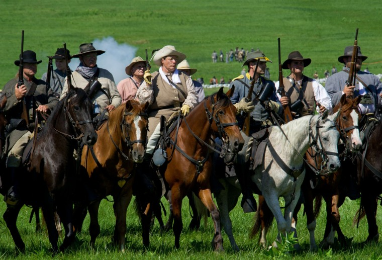 Confederate cavalry with weapons at the ready ride towards Union forces during a re-enactment of the Battle of Gettysburg on June 29, 2013, at the start of the 150th Gettysburg celebration in Gettysburg, Pennsylvania. (Karen Bleier/Getty Images)