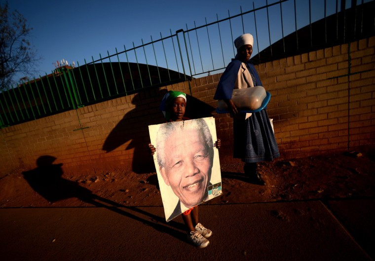 A woman and a little girl hold a Nelson Mandela picture in front of the Medi Clinic Heart hospital in Pretoria. Emotional crowds gathered outside the hospital where Nelson Mandela lay in critical condition Wednesday, as relatives and clan elders made preparations for the revered former South African leader's final journey. Singing supporters amassed outside the Pretoria hospital where the 94-year-old anti-apartheid hero was fighting for his life. (Filippo Monteforte/Getty Images)
