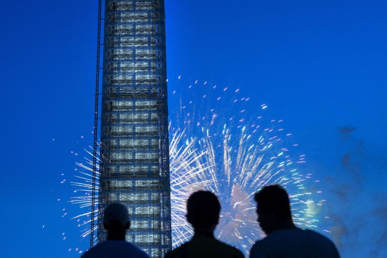 People watch fireworks burst behind the Washington Monument on the National Mall July 4, 2013 in Washington, DC. The United States celebrated the 237th anniversary of independence from the British Empire. (Brendan Smialowski/Getty Images)