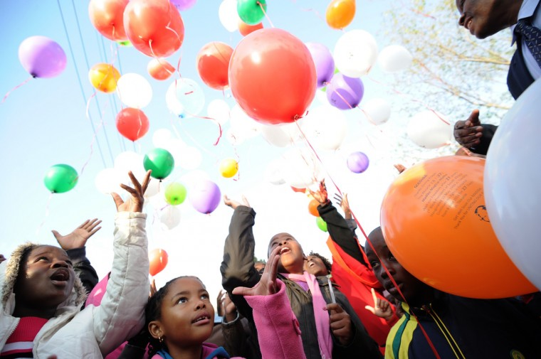 Kids release balloons after a prayer for former South African President Nelson Mandela outside the Medi Clinic Heart Hospital where Mandela is hospitalized in Pretoria. (Stephane de Sakutin/Getty Images)