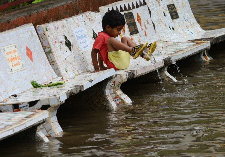 A child at the Shrinand Nagar Residency reacts to floodwaters in Ahmedabad, India. Heavy rains lashed many parts of Gujarat state with the Indian Meteorological Department predicting heavy rains for the next 24 hours. (Sam Panthaky/Getty Images)