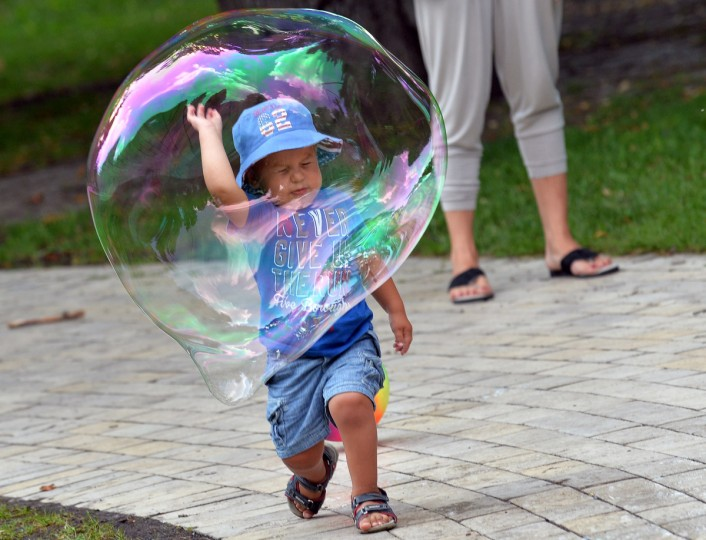 A boy plays with a soap bubble in one of Kiev parks on a hot day in the Ukrainian capital. (Sergei Supinsky/Getty Images)