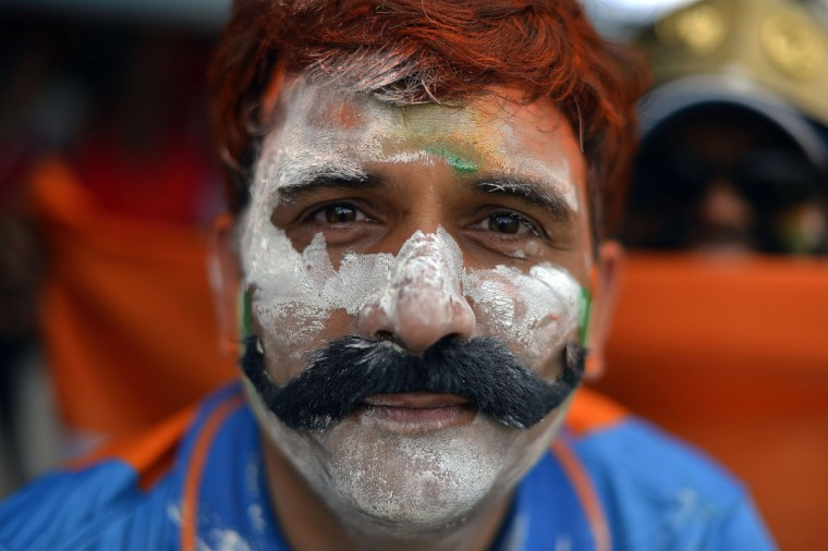 An Indian cricket fan has his face painted with national colors as he watches the fourth match of the Tri-Nation series between India and West Indies at the Queen's Park Oval in Port of Spain. (Jewel Samad/Getty Images)