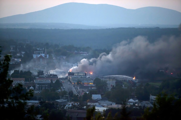 Firefighters douse blazes after a freight train loaded with oil derailed in Lac-Megantic in Canada's Quebec province on July 6, 2013, sparking explosions that engulfed about 30 buildings in fire. At least 80 people are missing after a driverless oil tanker train derailed and exploded in the small Canadian town of Lac-Megantic, destroying dozens of buildings. (Francois Laplante-Delagrave/Getty Images)