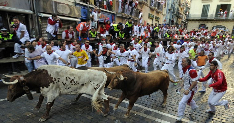 Participants run in front of Alcurrucen's bulls during the first bull run of the San Fermin Festival in Pamplona, northern Spain. (Rafa Riva/Getty images)