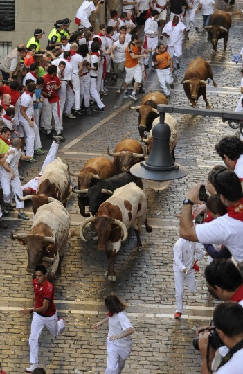 Participants run in front of Alcurrucen's bulls during the first bull run of the San Fermin Festival in Pamplona, northern Spain. (Pedro Armestre/Getty images)