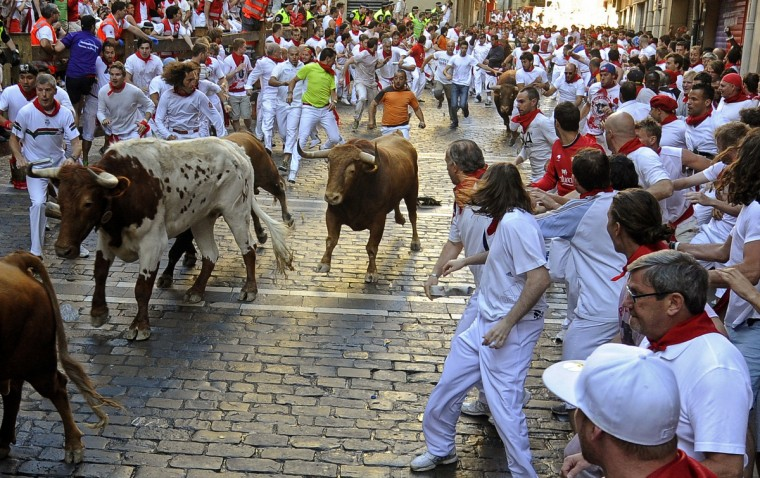 Participants run in front of Alcurrucen's bulls during the first bull run of the San Fermin Festival in Pamplona, northern Spain. The festival is a symbol of Spanish culture that attracts thousands of tourists to watch the bull runs despite heavy condemnation from animal rights groups. (Rafa Riva/Getty images)