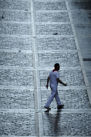 A participant walks down the Estafeta street before the first bull run of the Alcurrucen's bulls of the San Fermin Festival in Pamplona, northern Spain. (Pedro Armestre/Getty images)