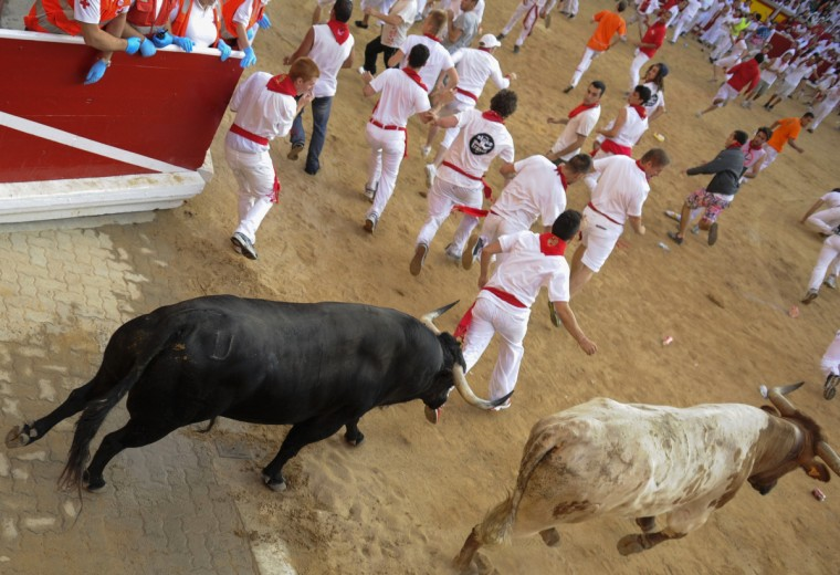 Participants run in front of Dolores Aguirre's bulls during a bull run of the San Fermin Festival in Pamplona, northern Spain. (Pedro Armestre/Getty images)