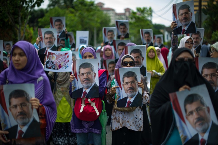 Malaysian Islamist protesters hold posters of ousted Egyptian President Mohamed Morsi during a protest to oppose the military overthrow of the Islamist leader and subsequent killings in Egypt, outside the Egyptian embassy in Kuala Lumpur. Fifty-one people, mostly Mohamed Morsi loyalists, were killed in Egypt on July 8 while rallying in favour of the ousted president, as the new rulers announced fresh elections by early 2014 amid US calls for restraint. (Mohd Rasfan/Getty Images)