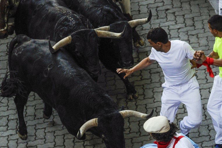Participants run in front of Valdefresno's bulls during the third bull run of the San Fermin Festival in Pamplona, northern Spain. (Pedro Armestre/Getty images)