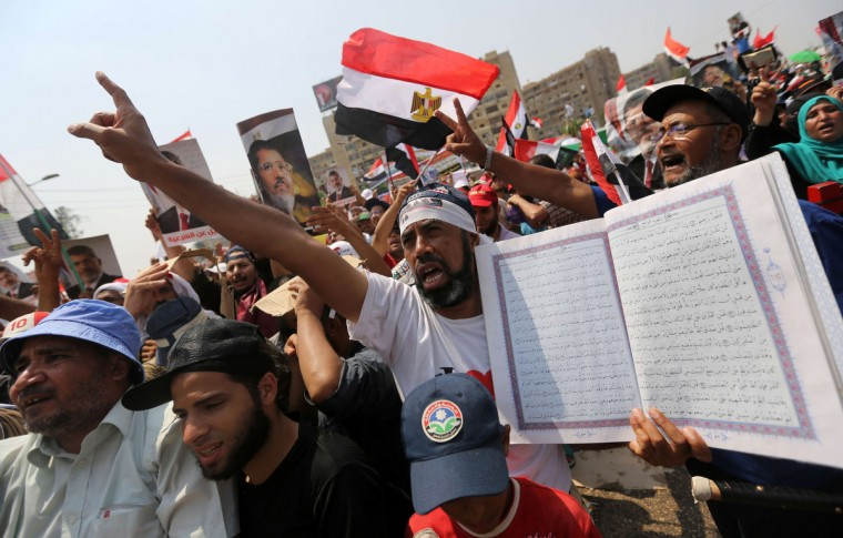 Egyptian supporters of deposed president Mohamed Morsi hold a copy of the Koran, Islam's holy book, and wave their national flag as they shout slogans during a rally in support of the former Islamist leader (portrait back-L) outside Cairo's Rabaa al-Adawiya mosque. Egypt's interim leader vowed fresh elections by early next year as Islamists staged fresh rallies after dozens of Morsi's loyalists died in clashes at a Cairo military barracks (Mahmud Hams/Getty Images)