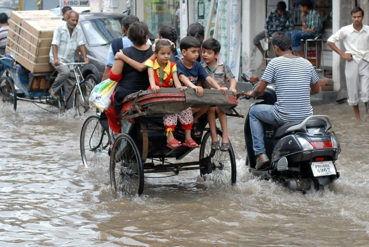 Indian commuters make their way through a waterlogged street after heavy monsoon rains fell in Jalandhar. Authorities have raised to 5,500 the estimated number of people who perished in devastating floods that swept the northern Indian state of Uttarakhand last month. (Shammi Mehra/Getty Images)