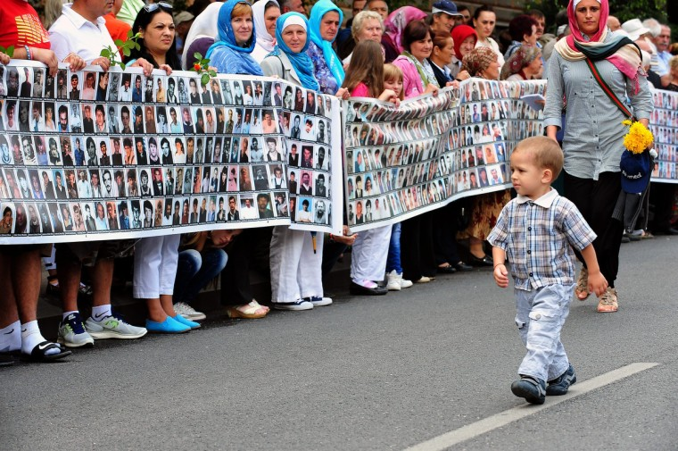 A Bosnian boy walks by women holding a banner with picture of people killed in Srebenica as they await the arrival of the trucks transporting body caskets of Srebrenica 1995 victims, from the municipal morgue in the Central-Bosnian town of Visok, in preparation for a mass burial, at Potocari Memorial cemetery near the Eastern-Bosnian town of Srebrenica, on July 11. The Potocari Memorial cemetery is undergoing preparations for another mass burral on July 11, when 408 newly identified bodies will be put to final rest. Bodies are identified as those belonging to Bosnian Muslim victims of the offensive undertaken by Bosnian Serbs in July 1995 with aim to occupy the earlier declared UN safe heaven area of Srebrenica and the surrounding villages. During the offensive more than 8000 Bosnian non-Serbs went missing to be found buried in mass graves, years after the war ended. (Elvis Barukcic/Getty Images)