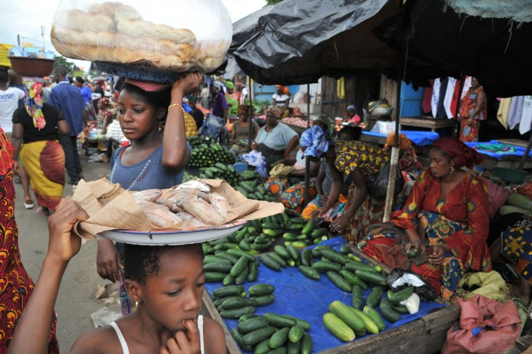 Women sells cucumbers as people carry fish and bread loaves on their heads in the market of Abobo, a suburb of Abidjan on July 9, 2013 on the first day of the Muslim holy month of Ramadan in Ivory Coast. The holy month of Ramadan, during which Muslims fast from dawn to dusk, begins with the sighting of the new moon, which varies from country to country. (Issouf Sanogo/Getty Images)
