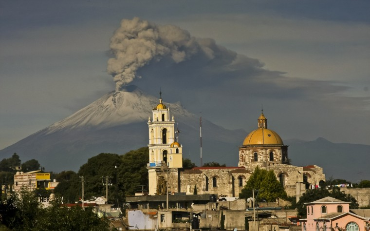"Ash spews from Mexico's Popocatepetl volcano, some 55 km from Mexico City, as seen from San Damian Texoloc in the Mexican central state of Tlaxcala. During the weekend authorities have raised the alert level to ""Yellow Phase Three,"" the fifth of a seven-stage warning system, restricting access to an area of 12 km around the volcano while preparing evacuation routes and shelters. (J.Guadalupe Perez/Getty Images)"