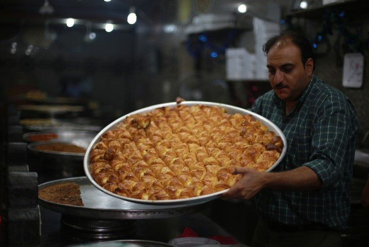 A pastry chef holds a tray of Arabic sweets at his bakery in Gaza City on the eve of the start of the holy Muslim fasting month of Ramadan, on July 9, 2013. During Ramadan, one of the five main religious obligations under Islam, Muslims are required to abstain from food and from drinking liquids, smoking and having sex from dawn until dusk. (Mohammed Abed/Getty Images)