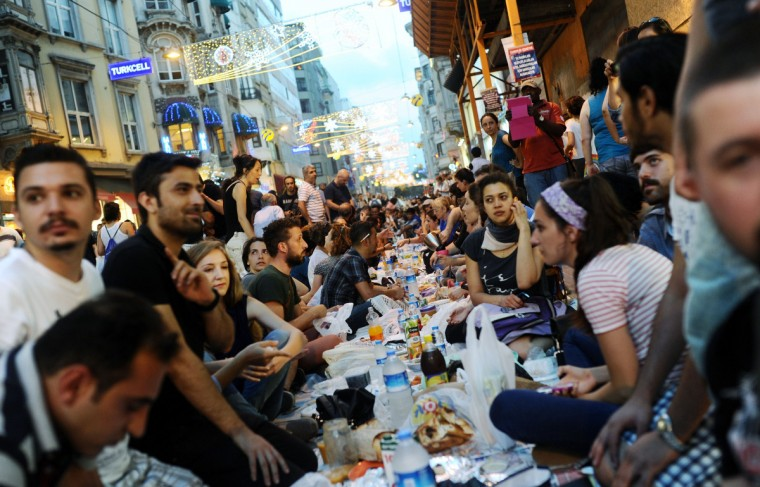 Turkish anti government protesters gather as they break their first day of fasting for the Muslim holy month of Ramadan on Istiklal street, the main shopping corridor, on July 9, 2013 in Istanbul. (Bulent Kilic/Getty Images)