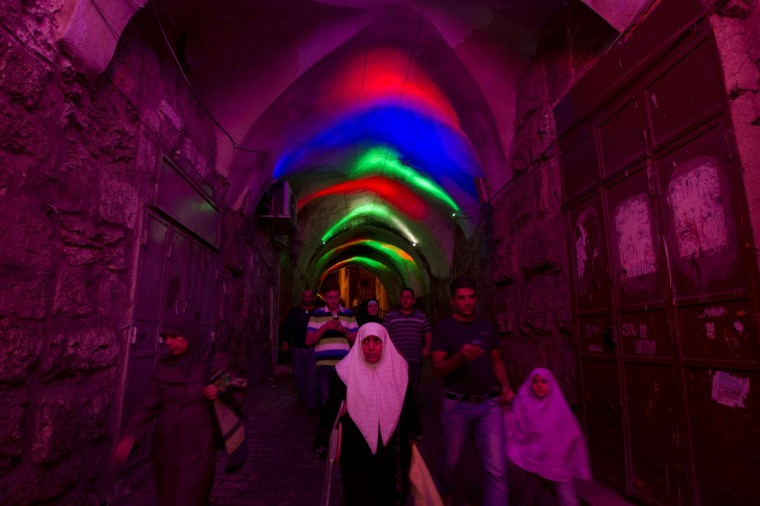 Palestinians walk before attending the evening prayer during the Muslim fasting month of Ramadan at the Al-Aqsa mosque compound in the old city of Jerusalem on July 9, 2013. During Ramadan, one of the five main religious obligations under Islam, Muslims are required to abstain from food and from drinking liquids, smoking and having sex from dawn until dusk. (Ahmad Gharabli/Getty Images)