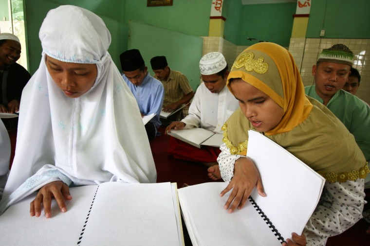 Indonesian disabled students reads a copy of a Koran with braille alphabet on the first day of the holy month of Ramadan in Malang city East Java on July 10, 2013. Islam's holy month of Ramadan is celebrated by Muslims worldwide marked by fasting, abstaining from foods, sex and smoking from dawn to dusk for soul cleansing and strengthening the spiritual bond between them and the Almighty. (Aman Rochman/Getty Images)