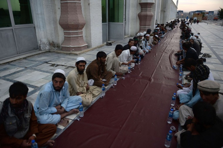 Afghan men wait for their free evening meal during Iftar at the Eidga mosque in Kabul on July 10, 2013, during the Islamic month of Ramadan. Throughout the month devout Muslims must abstain from food, drink and sex from dawn until sunset when they break the fast with the Iftar meal. (Shah Marai/Getty Images)
