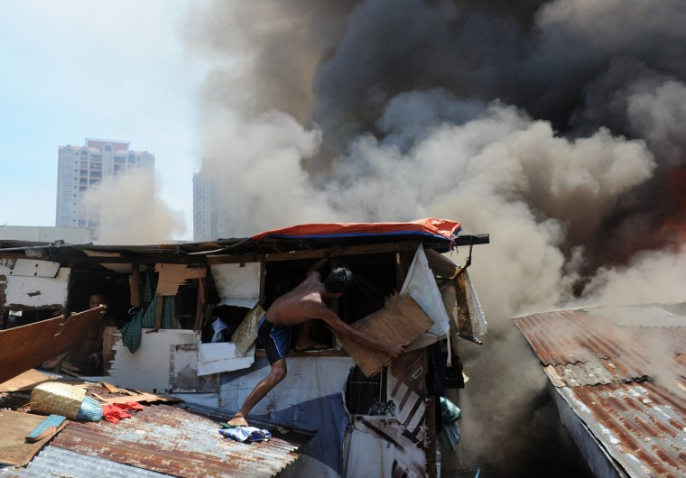 A resident destroys a wall of his house in an effort to salvage belongings as a fire engulfs a shanty town in the financial district of Manila, leaving more than 1,000 people homeless according to city officials. There were no immediate reports of casualties from the blaze, which occurred mid-morning amid government plans to relocate thousands of families living in areas vulnerable to floods and typhoons. (Ted Aljibe/Getty Images)
