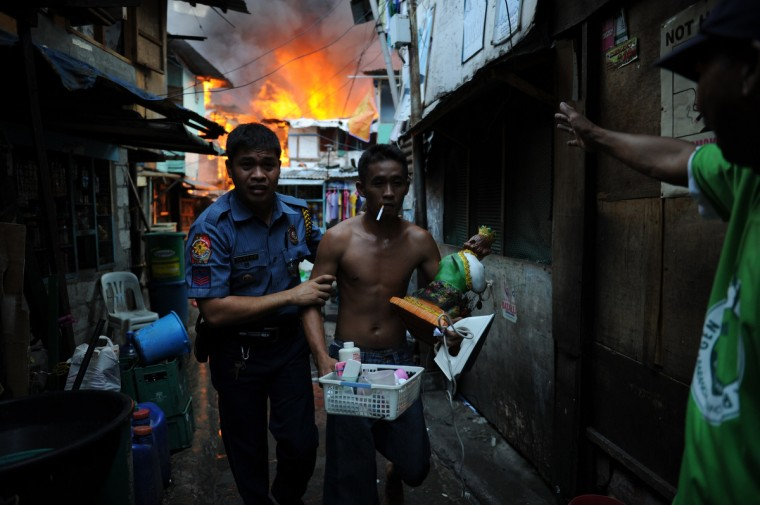 A policeman (L) leads out a resident carrying salvaged belongings from his burning house as a fire engulfs a shanty town in the financial district of Manila, leaving more than 1,000 people homeless according to city officials. There were no immediate reports of casualties from the blaze, which occurred mid-morning amid government plans to relocate thousands of families living in areas vulnerable to floods and typhoons. (Ted Aljibe/Getty Images)