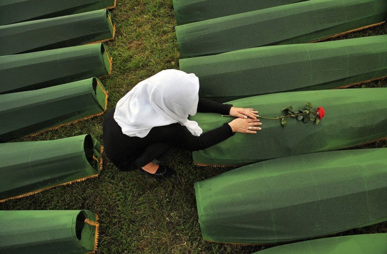 A Bosnian Muslim woman, survivor of Srebrenica 1995 massacre, mourns over body casket of her relative, at memorial cemetery in village of Potocarion near Eastern-Bosnian town of Srebrenica. Potocari Memorial cemetery is undergoing preparations for another mass burial on July 11, when 409 newly identified bodies will be put to final rest. Bodies are identified as those belonging to Bosnian Muslim victims, of the offensive undertaken by Bosnian Serbs in July 1995 with aim to occupy, earlier declared UN safe heaven area of Srebrenica and the surrounding villages. During the offensive more than 8000 Bosnian non-Serbs went missing to be found buried in mass graves, years after the war ended. (Elvis Barukcic/Getty Images)