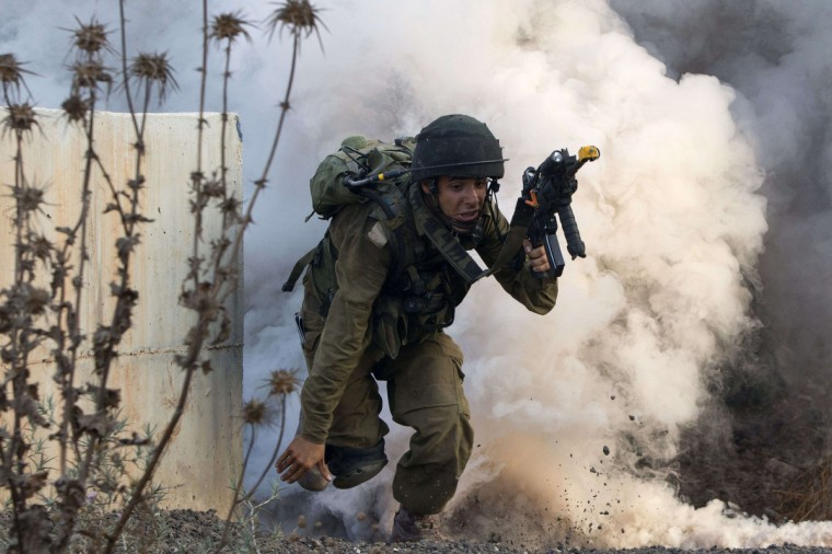 An Israeli infantry soldier from the Kfir Brigade takes part in a drill in urban warfare simulating a combat mission with Lebanon's Hezbollah at the Israeli army base of Elyakim in northern Israel. Israeli military built the training base at Elyakim to train soldiers on how to fight Hezbollah as Israel bolsters security along its border with Syria, where Hezbollah militants are reportedly fighting alongside government forces against rebels. (Jack Guez/Getty Images)