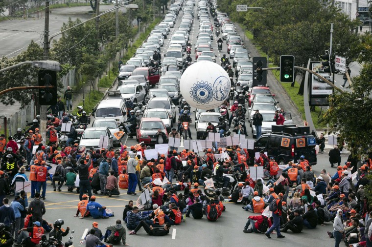 Members of various labour unions block a street, in Sao Paulo, Brazil, during a protest to lower public transport rates, to increase public investments in health and education, to reduce working hours and land reform, among other claims. (Miguel Schincariol/Getty Images)