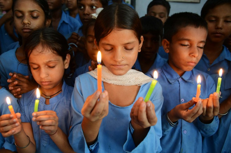Indian school children hold candles as they payi tribute to school children that died from food poisoning in Saran district of Bihar state, at a government school in Amritsar. Thousands of schoolchildren were refusing free meals in poverty-stricken eastern India after 22 children died from eating lunch apparently contaminated with insecticide, officials said. (Narinder Nanu/Getty images)