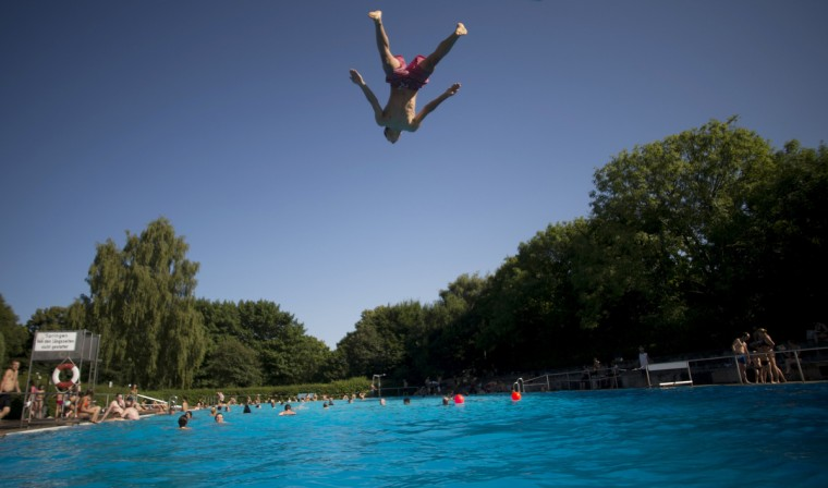 A boy jumps into the water of a public swimming pool in Berlin's Neukoelln district as temperatures in the capital reached 30 degrees Celsius. (Johannes Eisele/Getty images)