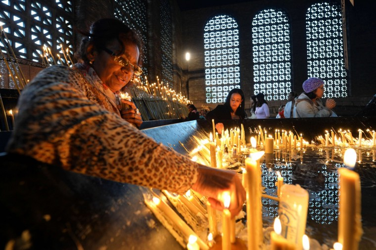 Faithful light candles at the Basilica and National Sanctuary of Our Lady of Aparecida -which will be visited by Pope Francis Wednesday- in Aparecida, Sao Paulo state, Brazil. Pope Francis's popularity on his Latin American home turf posed a challenge to Brazilian authorities after adoring crowds mobbed his car on his landmark visit during the World Youth day (WYD) to Rio de Janeiro. (Nelson Almeida/Getty images)