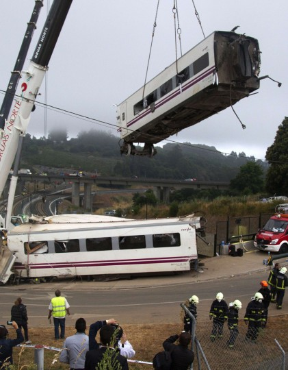 A crane removes a derailed train's car at the site of a train accident near the city of Santiago de Compostela on July 25, 2013. A train hurtled off the tracks on July 24, 2013 in northwest Spain killing at least 77 passengers and injuring more than 140, an official said today, the country's deadliest rail disaster in more than 40 years. (Stringer/Getty images)