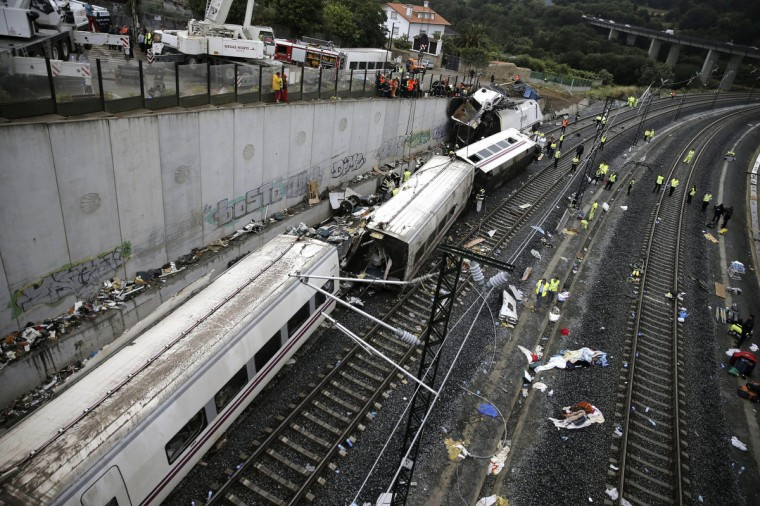 Rescuers, forensics and police officers work at the site of a train accident near the city of Santiago de Compostela on July 25, 2013. A train hurtled off the tracks on July 24, 2013 in northwest Spain killing at least 77 passengers and injuring more than 140, an official said today, the country's deadliest rail disaster in more than 40 years. (Emilio Lavandeira/Getty images)