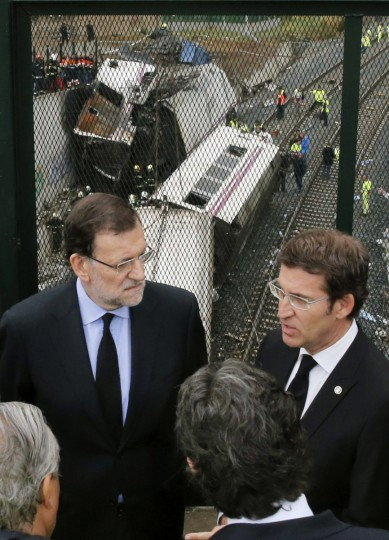 Spanish Prime Minister Mariano Rajoy (L) and Galicia's regional President Alberto Nunez Feijoo (R) visit the site of a train accident near the city of Santiago de Compostela on July 25, 2013. A train hurtled off the tracks on July 24 in northwest Spain killing at least 77 passengers and injuring more than 140, an official said today, the country's deadliest rail disaster in more than 40 years. (Lavandeira Jr/Getty images)
